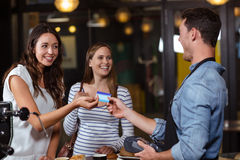 Smiling clients paying with card. At the bar stock images