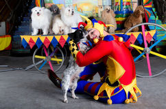 Smiling clown embraces his dog Royalty Free Stock Image