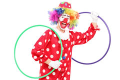 Smiling clown holding two hula hoops. Isolated on white background Stock Photography