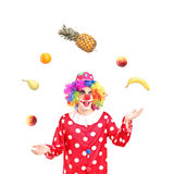 A smiling clown juggling fruits. Isolated against white background Royalty Free Stock Photography