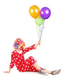 Smiling clown sitting and holding balloons Royalty Free Stock Image