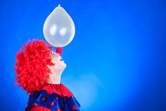 Smiling clown in studio with balloon Royalty Free Stock Image