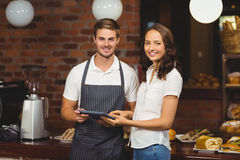 Smiling co-workers holding a tablet. Portrait of co-workers holding a tablet at the coffee shop Stock Photo
