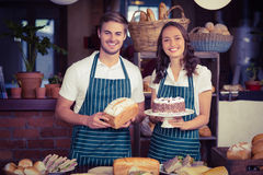 Smiling co-workers showing bread and cake Stock Photo