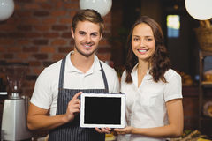 Smiling co-workers showing a tablet Royalty Free Stock Photo