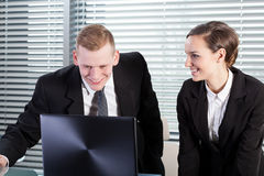 Smiling co-workers using laptop Stock Images