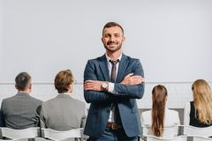 Smiling coach with crossed arms looking at camera during business training. In hub royalty free stock photo