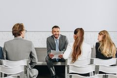 Smiling coach looking at business people during training. In hub royalty free stock photo