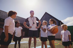 Smiling coach and schoolkids interacting with each other. In schoolyard Stock Photography