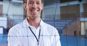 Smiling coach standing with arms crossed behind the net 4k. Portrait of smiling coach standing with arms crossed behind the net 4k stock footage