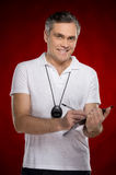 Smiling coach standing on red background. Stock Photography