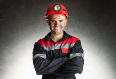 Smiling coal miner. Portrait of happy smiling coal miner with his arms crossed against a dark background Royalty Free Stock Images