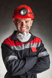 Smiling coal miner. Portrait of happy smiling coal miner with his arms crossed against a dark background Royalty Free Stock Photo