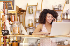 Smiling coffee shop owner typing on a laptop while talking. Happy young coffee shop owner talking on he mobile phone while typing on her laptop on the counter Stock Image