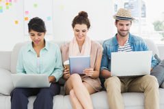 Smiling colleagues on couch using laptop and tablet Royalty Free Stock Image