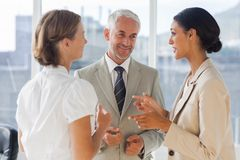 Smiling colleagues discussing together stock photo