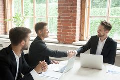 Smiling colleagues greeting each other with handshakes. Smiling colleagues greet each other with handshakes. Corporate coworkers meeting or closing deal royalty free stock photos