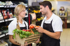 Smiling colleagues holding a box with fresh vegetables. At supermarket Stock Photo