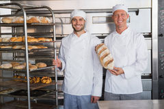 Smiling colleagues holding fresh loaves Royalty Free Stock Image