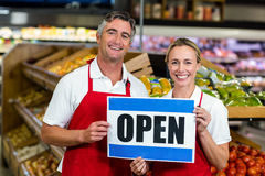 Smiling colleagues holding sign together Stock Images