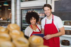 Smiling colleagues holding tablet pc. At the bakery Royalty Free Stock Photos