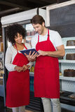 Smiling colleagues in red apron using tablet together Royalty Free Stock Photo