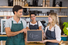 Smiling colleagues showing chalkboard with open sign Stock Images