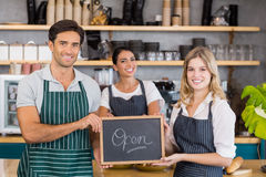 Smiling colleagues showing chalkboard with open sign Royalty Free Stock Photography