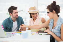 Smiling colleagues speaking together at desk Stock Photo