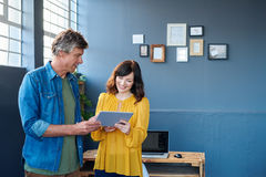 Smiling colleagues talking together over a tablet in an office Stock Photos
