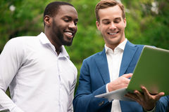 Smiling colleagues using laptop. Emotionally charged. Positive content smiling colleagues using laptop and expressing gladness while standing outside stock photos