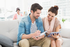 Smiling colleagues using tablet and taking notes on couch Stock Photography