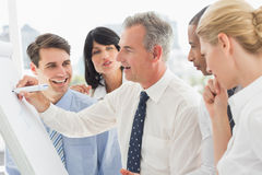 Smiling colleagues watching businessman writing on whiteboard Stock Photo