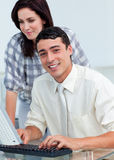 Smiling colleagues working together at a computer Royalty Free Stock Images