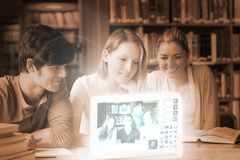 Smiling college friends watching photos on digital interface Royalty Free Stock Images
