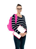 Smiling college girl carrying school bag Stock Photos