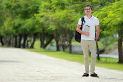 Smiling college student with backpack holding a tablet Royalty Free Stock Photo