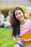 Smiling college student with blurred friends in park Stock Photography