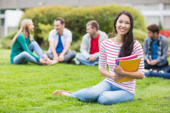 Smiling college student with blurred friends sitting in the park Royalty Free Stock Photo