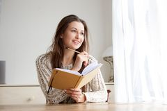 Smiling college student with book and pencil Royalty Free Stock Photography