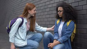 Smiling college student encouraging new classmate taking hand, help assistance