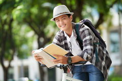 Student with book. Smiling college student leaning on handlebar and reading a book Stock Photography