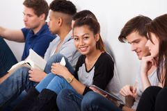 Smiling college student sitting with classmates. Portrait of smiling female college student sitting with classmates against wall in classroom Royalty Free Stock Photos