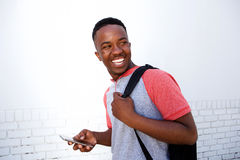Smiling college student walking with bag and mobile phone. Side portrait of smiling college student walking with bag and mobile phone Stock Photo