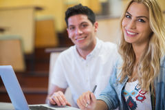 Smiling college students using laptop Royalty Free Stock Photos