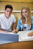 Smiling college students using laptop Royalty Free Stock Photo
