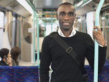 Smiling Commuter Standing In Train Royalty Free Stock Images