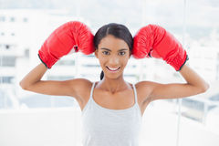Smiling competitive model wearing red boxing gloves Royalty Free Stock Photo