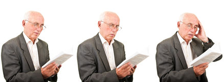 Smiling, concerned, worried senior man reading Royalty Free Stock Photography
