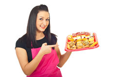 Smiling confectioner pointing to cakes Royalty Free Stock Image
